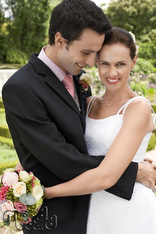 Mid adult bride and groom in garden embracing