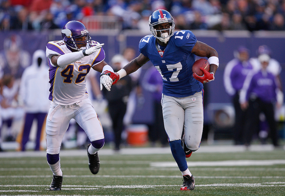 EAST RUTHERFORD, NJ - NOVEMBER 25: Plaxico Burress #17 of the New York Giants runs with the ball while being chased by Darren Sharper #42 of the Minnesota  during their game at Giants Stadium on November 25, 2007 in East Rutherford, New Jersey. The Vikings defeated the Giants 41 to 17