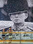 "06 NOVEMBER 2016 - BANGKOK, THAILAND: Thais stand in front of a large mosaic photo of Bhumibol Adulyadej, the late King of Thailand at the Bangkok Art and Culture Centre. The Royal Photographic Society of Thailand with the Bangkok Art and Culture Centre and Thai Beverage Public Company Limited are hosting a photography exhibition to commemorate the late Thai King Bhumibol Adulyadej. The ""In Remembrance of His Majesty King Bhumibol Adulyadej"" Photography Exhibition is dsiplaying 89 photographs by 89 photographers honoring King Bhumibol Adulyadej's legacy. The King was an avid photographer was usually seen with a camera in his hands. The exhibition will be on display until 27 November 2016 on the Curved Walls on the 3rd - 5th floor, Bangkok Art and Culture Centre.     PHOTO BY JACK KURTZ"