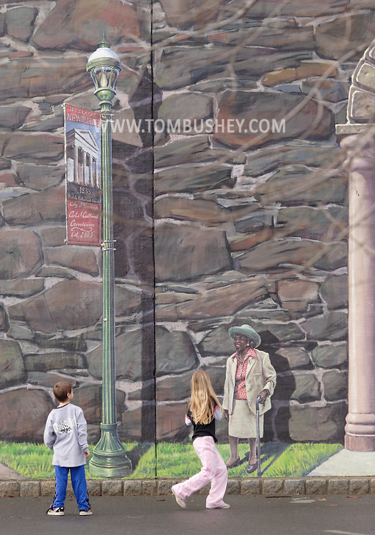 """Newburgh, NY -Two children look at a section of the """"Arches of Newburgh"""" mural painted on the CSX Railroad trestle on the Newburgh waterfront on Feb. 5, 2008. The 220-foot long mural was painted by Garin Baker."""