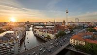 Die Berliner Skyline mit dem Fernsehturm, Rote Rathaus, Berliner Dom sowie Teilen des Spreeufers bei Sonnenuntergang.