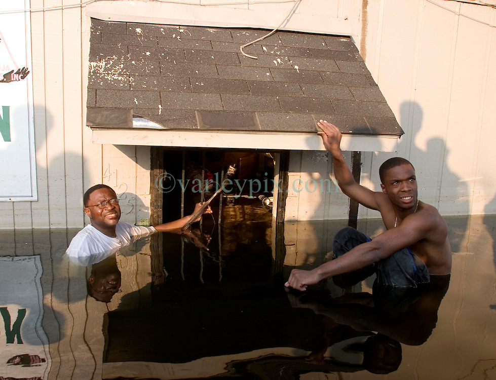 05 Sept  2005. New Orleans, Louisiana. Post hurricane Katrina.<br /> L/R Jonas Smith and his father John swim through the murky water in Uptown New Orleans as the family attempt to rescue their business.<br /> Photo; ©Charlie Varley/varleypix.com