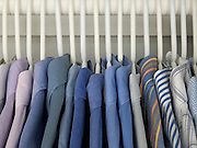 men shirts hanging in a closet.