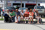 Group of adults sitting on bench waiting for the bus or tram. Warsaw Poland