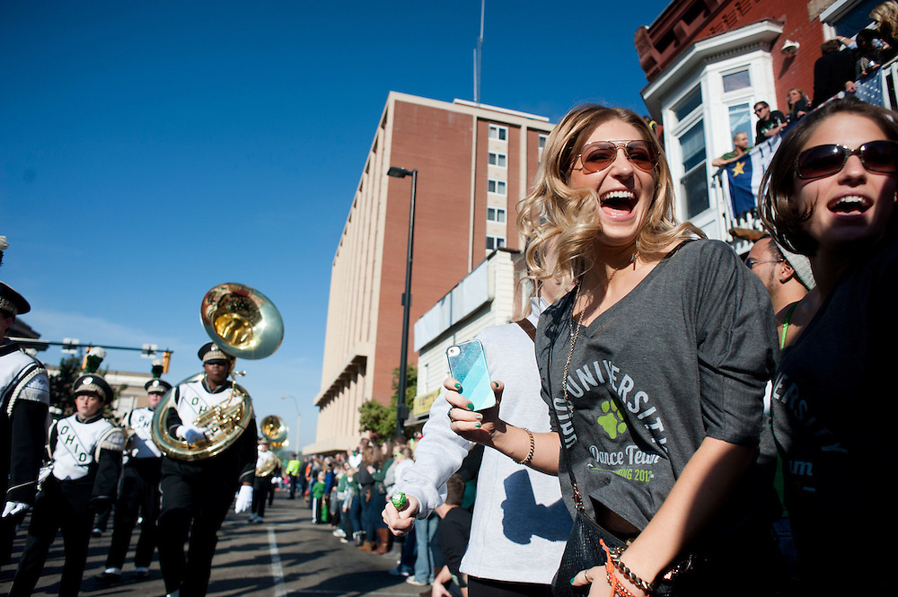 Amanda Yezerski, an OU alumni (center) and Claire Oby celebrate as the Marching 110 passes by during the homecoming parade. Photo by: Ross Brinkerhoff..