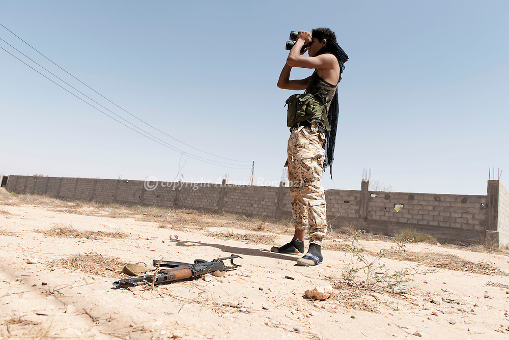 Libya: A fighter sympathising with Libya's Government of National Accord's (GNA) looks with a binoculars at ISIS positions on the frontline in Sirte. Alessio Romenzi