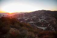 The sun sets over the SoCalGas Aliso Canyon Storage Facility, looking towards where a leaking gas well and a relief well are being drilled, at the top of a public hiking trail from Bee Canyon Park as methane gas leaks from the SoCalGas Aliso Canyon Storage Facility well SS-25 in the Porter Ranch neighborhood of Los Angeles, California on Wednesday, December 30, 2015. The Aliso Canyon gas leak (also called Porter Ranch gas leak) was a massive natural gas leak that started on October 23, 2015. According to Wikipedia, an estimated 1,000,000 barrels per day was released from a well within the underground storage facility in the Santa Susana Mountains near Porter Ranch. The second-largest gas storage facility it belongs to the Southern California Gas Company (SoCalGas), a subsidiary of Sempra Energy. On Jan. 6, 2016, Governor Jerry Brown issued a State of Emergency. The Aliso gas leak carbon footprint is said to be larger than the Deepwater Horizon leak in the Gulf of Mexico. On Feb. 11, 2016 the gas company reported that it had the leak under control. On Feb. 18 state officials announced that the leak was permanently plugged. An estimated 97,100 tonnes of methane and 7,300 tonnes of ethane was released into the atmosphere, making it the worst natural gas leak in U.S. history in terms of its environmental impact. © 2015 Patrick T. Fallon