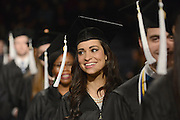 A Kent State graduate smiles as she files into the MACC for the Fall 2014 Commencement.