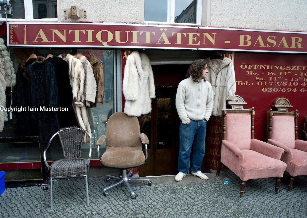 Shopkeeper standing outside his antiques shop in Bergmannstrasse in bohemian part of Kreuzberg in Berlin Germany 2008
