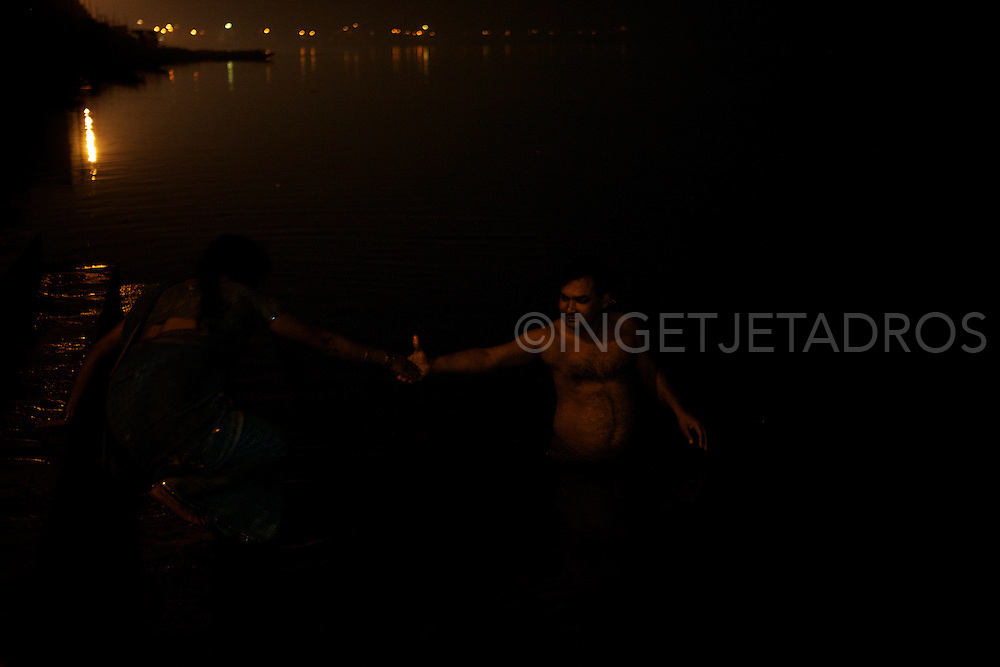 A man is helping his wife to enter the Holy River Ganges to bath and pray.<br />