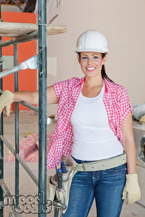 Portrait of happy architect wearing hardhat standing at construction site