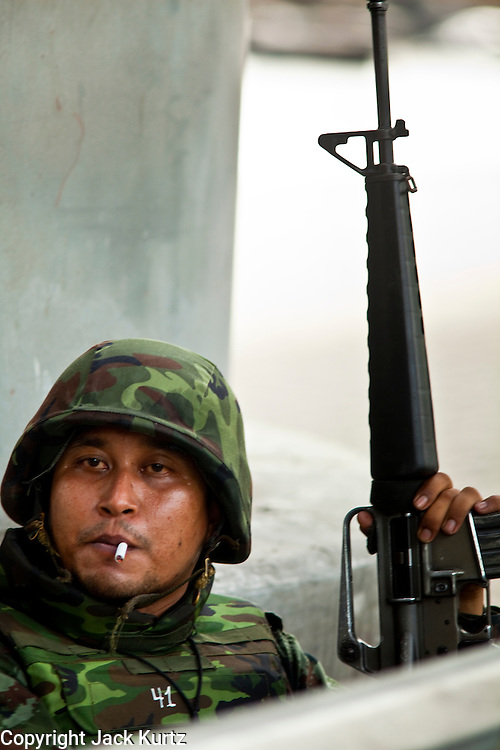 May 19 - BANGKOK, THAILAND: A Thai soldier takes a smoking break during the attack on Lumpini Park during the Thai government crack down against Red Shirt and anti government protesters. The Royal Thai Army attacked anti-government protesters May 19 with troops and armored personnel carriers. Photo by Jack Kurtz