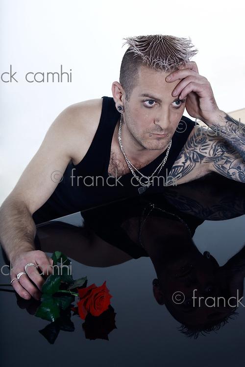 studio shot of a sad romantic  man  with tatoos and piercing