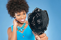 Young woman holding looking at mirror over colored background