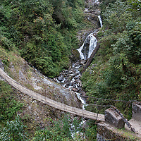 Walking on a wooden suspension bridge before reaching Melamchi village.