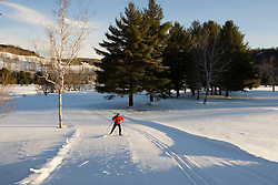 A man cross-country skiing (skate skiing) on a groomed trail in Quechee, Vermont.