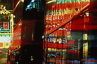 Hong Kong, Kowloon, Nathan Road, Neon lights reflected on double decker buses.