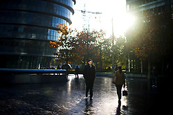 © London News Pictures. 05/11/2012. London, UK.  Commuters making their way to work in bright Autumn sunshine in front of  City Hall on the Southbank of the River Thames in London on November 05, 2012. Photo credit: Ben Cawthra/LNP.