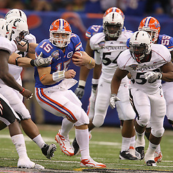 Jan 01, 2010; New Orleans, LA, USA;  Florida Gators quarterback Tim Tebow (15) is pursued by a group of Cincinnati Bearcats defenders during the second half of the 2010 Sugar Bowl at the Louisiana Superdome.  Mandatory Credit: Derick E. Hingle-US PRESSWIRE.
