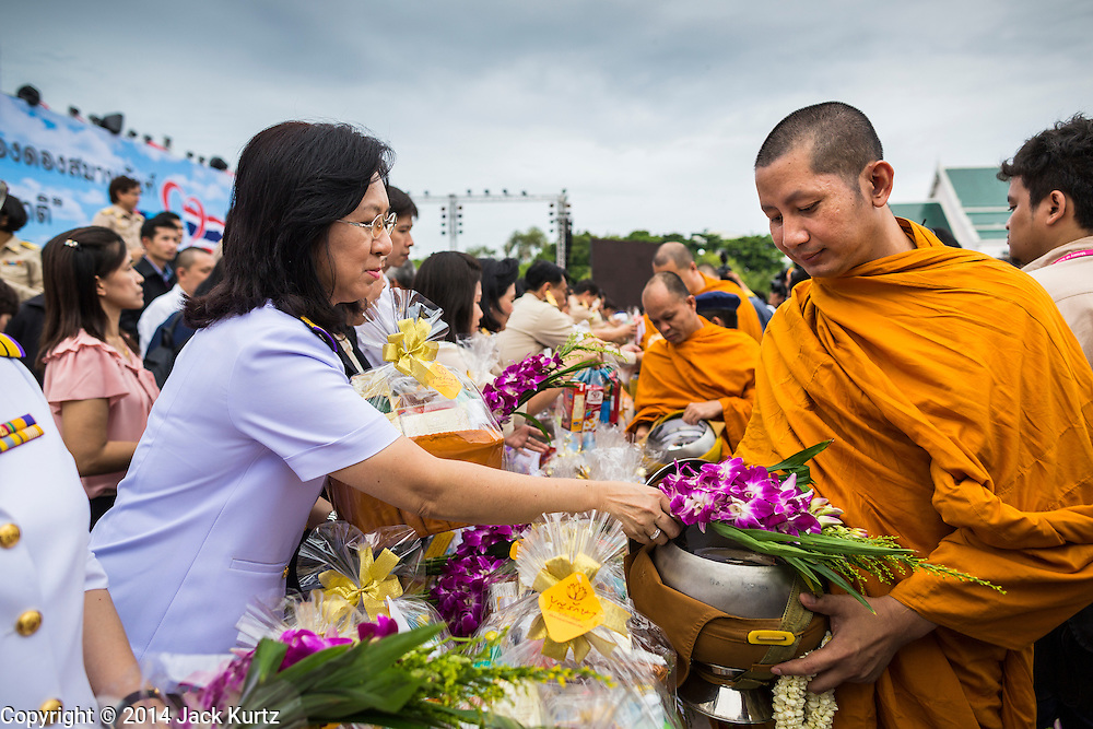 """22 JULY 2014 - BANGKOK, THAILAND: Thai officials make merit by presenting alms to Buddhis monks during a merit making ceremony at Sanam Luang. Hundreds of Thai military officers and civil servants attended a Buddhist chanting service and merit making ceremony to mark the 2nd month anniversary of the May 22 coup that deposed the elected civilian government and ended nearly six months of sometimes violent anti-government protests. The ruling junta said the ceremonies Tuesday were the kickoff to a """"Festival to Bring Back Happiness of the People of the Nation."""" There will be free concerts, historical pageants and movies at Sanam Luang, a large parade ground near the Ministry of Defense in Bangkok.    PHOTO BY JACK KURTZ"""