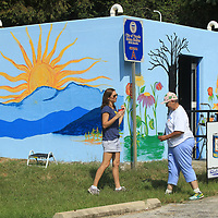Kathryn Rhea, Director of Keep Tupelo Beautiful, Nettie Davis, Tupelo Ward 4 Councilwoman, and Belle Naugher, Director of the GumTree Museum of Art, work together on painting a mural on the storm shelter on Front Street in Tupelo Wednesday. The project, started by Davis, is to beautify the shelter in conjunction with Keep Tupelo Beautiful.