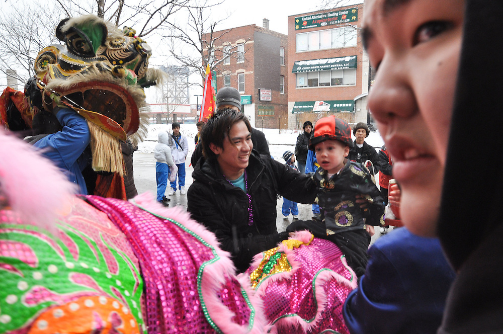 A bewildered child gets a ride on the back of the lion. Chinese New Year, Chinatown, Chicago, February 6th, 2011