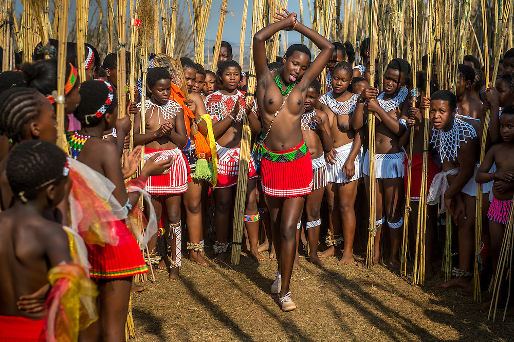 Young women dancing in a circle at the Reed Dance-Ludzidzini, Swaziland, Africa - The Swazi Umhlanga, or reed dance ceremony, 100,000 unmarried women , or maidens, celebrate their virginity by bringing reeds for the Swazi Queen Mother's Kraal during this 8 day long annual tradition and dancing in a massive gathering before King Mswati III, the royal family, and the public.