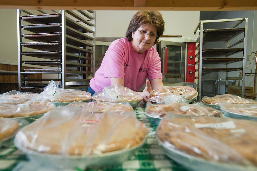 Woman behind table of apple pies
