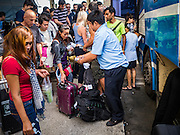 "03 JANUARY 2017 - BANGKOK, THAILAND:        People line up at Ekkamai Bus Station to get on a bus heading out of Bangkok. Travelers flocked to Bangkok bus and train stations Tuesday, the last day of the long New Year's weekend in Thailand. The New Year holiday in Thailand is called the ""seven deadly days"" because of the number of fatal highway and traffic accidents. As of Monday Jan 2, 367 people died in highway accidents over the New Year holiday in Thailand, a 25.7% increase over the same period in 2016.    PHOTO BY JACK KURTZ"