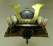 Helmet, iron with gilded copper decoration and stencilled leather; neck -guard of lacquered leather plates laced with silk.  Signed Myochin Nobuie, guardian of Echizer province of the Sano manor in Shimotsuke province on a day in the fourth month of the nineth year of Eisho (1512).  Half mask Iron - about 1700-1800.