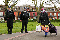 © Licensed to London News Pictures. 03/04/2020. London, UK. Police officers speak with a woman wearing a face mask in Duckett's Common as they patrol Wood Green High Road in north London. The Government has ordered that people should go out only for food and health reasons or for work, and keep 2 meters away from other people at all times to slow the spread of the virus and reduce pressure on the NHS. Photo credit: Dinendra Haria/LNP
