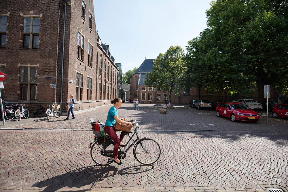 In Utrecht fietst een vrouw met veel tassen op de kinderzitjes door de binnenstad.<br /> <br /> In Utrecht cyclist ride at the city center.