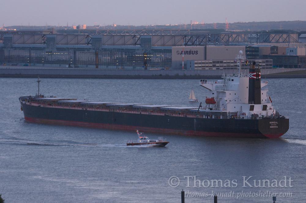 Mit Kohleladung bestimmt für das Terminal Hansaport am 24.09.2009. LOTSE 4 bringt den Hafenlotsen. Ein Segler begleitet längsseits. Am Deckshaus und am Horizont ein Lichtschein der Abendsonne.