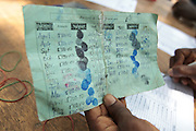 Project staff hold a beneficiary card during a UNICEF-sponsored social cash transfer programme distribution in the village of Julijuah, Bomi county, Liberia on Tuesday April 3, 2012. Beneficiary households receive monthly transfers that vary according to the size of the household, with additional sums provided for each child enrolled in school. Families are selected for participation in the programme based on two key criteria: they must be both extremely poor and labour-constrained.