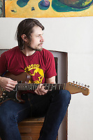 Young man sits playing electric guitar
