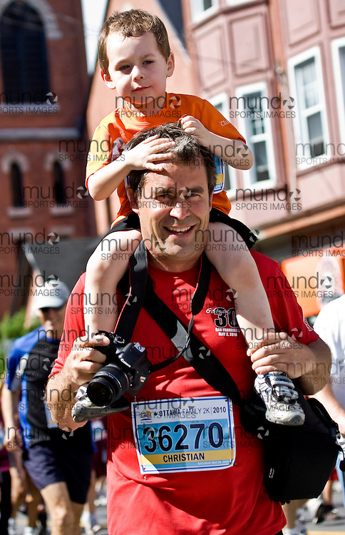 (Ottawa, ON --- May 29, 2010) Chritian Heroux carries an extra load and enjoys the experience of the  2km community race during the Ottawa Race Weekend. Photograph copyright Sean Burges / Mundo Sport Images