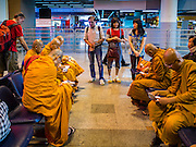 "23 FEBRUARY 2016 - BANGKOK, THAILAND: People talk to Buddhist monks in the departures lobby at Don Mueang International Airport. Nok Air, partly owned by Thai Airways International and one of the largest and most successful budget airlines in Thailand, cancelled 20 flights Tuesday because of a shortage of pilots and announced that other flights would be cancelled or suspended through the weekend. The cancellations came after a wildcat strike by several pilots Sunday night cancelled flights and stranded more than a thousand travelers. The pilot shortage at Nok comes at a time when the Thai aviation industry is facing more scrutiny for maintenance and training of air and ground crews, record keeping, and the condition of Suvarnabhumi Airport, which although less than 10 years old is already over capacity, and facing maintenance issues related to runways and taxiways, some of which have developed cracks. The United States' Federal Aviation Administration late last year downgraded Thailand to a ""category 2"" rating, which means its civil aviation authority is deficient in one or more critical areas or that the country lacks laws and regulations needed to oversee airlines in line with international standards.        PHOTO BY JACK KURTZ"