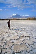 A Masai man walks the dried-out surface of Lake Natron with Ol Doinyo Lengai (The Mountain of God - the tribe's holy mountain) in the background.