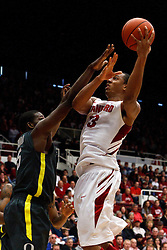 Feb 19, 2012; Stanford CA, USA; Stanford Cardinal forward/center Josh Owens (13) shoots over Oregon Ducks forward Olu Ashaolu (5) during the first half at Maples Pavilion.  Mandatory Credit: Jason O. Watson-US PRESSWIRE