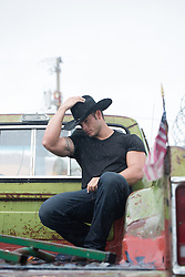 handsome All American cowboy in a black tee shirt, jeans and cowboy hat on an old pick up truck