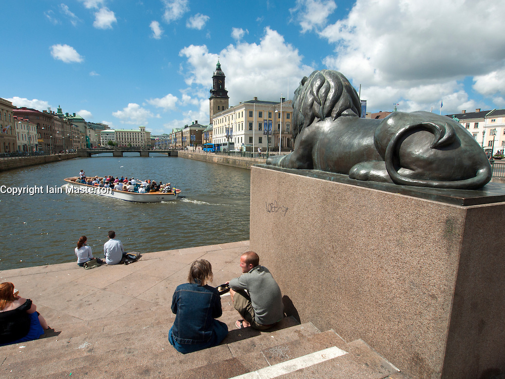 People sitting by waterside beside bronze lion guarding canal in central Gothenburg Sweden