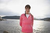 Woman standing by ocean portrait