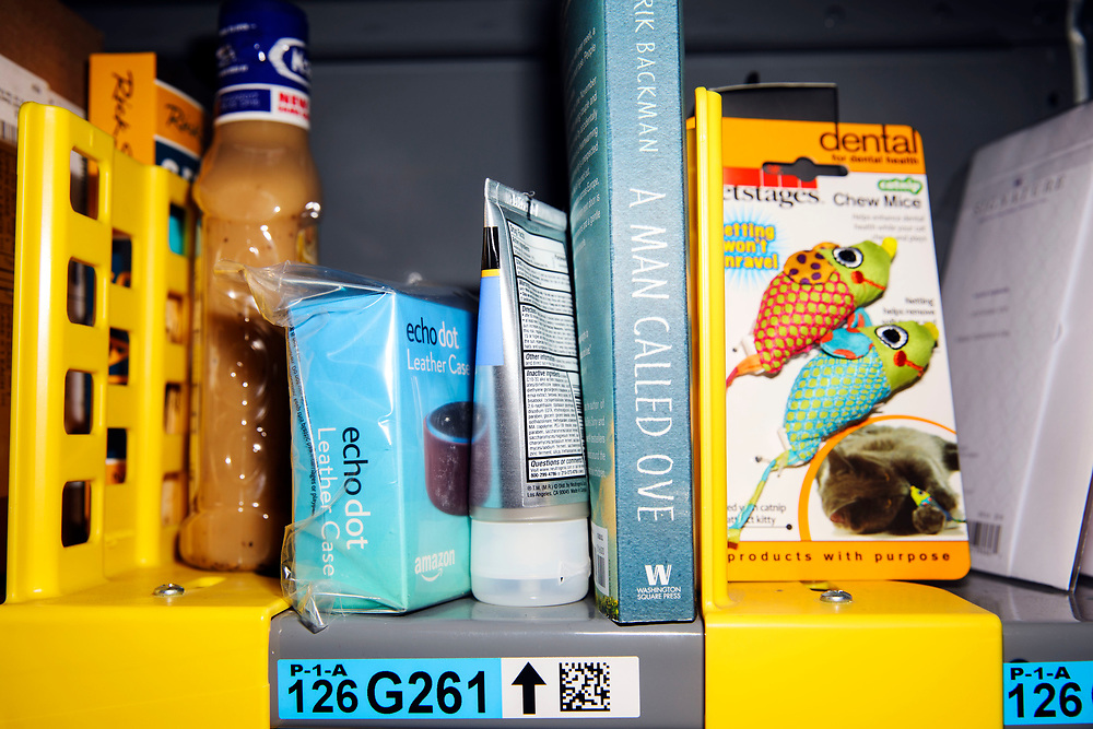 "A variety of items including salad dressing, an Amazon echo dot leather case, skin cream, the novel ""A Man Called Ove"" by Fredrik Backman, and chew mice cat toys, rest on shelves before they are ordered, picked, and delivered at the Amazon.com Inc. Prime Now fulfillment center warehouse on Monday, March 27, 2017 in Los Angeles, Calif. The warehouse can fulfill one and two hour delivery to customers. Complex supply chains such as Amazon's and e-commerce trends will impact city infrastructure and how things move through cities. © 2017 Patrick T. Fallon"