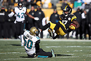 Pittsburgh Steelers wide receiver Eli Rogers (17) gets upended by Jacksonville Jaguars outside linebacker Telvin Smith (50) as he goes airborne to catch a first quarter pass for a gain of 13 yards and a first down at the Jaguars 30 yard line during the NFL 2018 AFC Divisional playoff football game against the Jacksonville Jaguars, Sunday, Jan. 14, 2018 in Pittsburgh. The Jaguars won the game 45-42. (©Paul Anthony Spinelli)