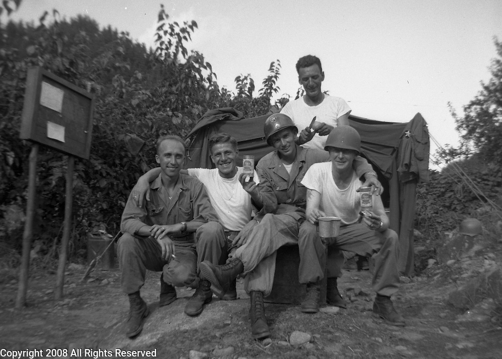 Officers of the Second Infantry Division relax for a group photo while drinking their beer ration in a break from Korean WAr fighting. These are photos of the 2nd Infantry Division in the Korean War in 1950 or 1951.