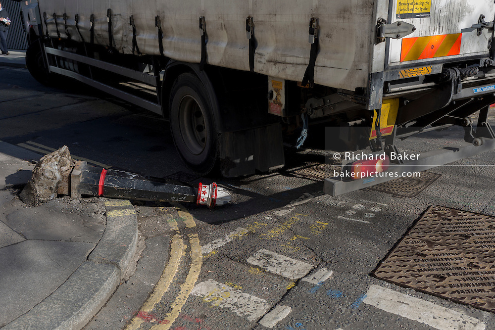 A detail of the road surface where a damaged bollard lies horizontal, knocked over by a vehicle on 13th February 2017, in the City of London, United Kingdom.