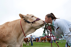 © Licensed to London News Pictures. 23/07/2018. Llanelwedd, UK. Cattle handler Student Minty Mayhew from Bristol, gives some affection to a 'Blonde' cow called Madhu (owned by David Knight)  on the first day of the Royal Welsh Agricultural Show. The Royal Welsh Agricultural Show is hailed as the largest & most prestigious event of its kind in Europe. In excess of 200,000 visitors are expected this week over the four day show period. The first ever show was at Aberystwyth in 1904 and attracted 442 livestock entries. Photo credit: Graham M. Lawrence/LNP