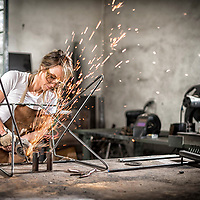 Furniture maker Greta de Parry grinds the metal legs of a Coleman stool. Photo by Jim Prisching
