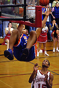 Benson's Drew Dukeshire #31 hangs from the rim while reaching for the tip in at the buzzer in overtime versus Lincoln on Friday night. He couldn't complete the basket and  the game went into double overtime. Lincoln's Dominique DeWeese and the crowd look on in amazement.