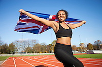Happy young female athlete holding up British flag on running track